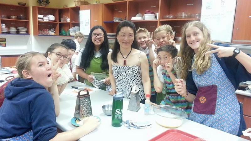 Ying and the students in her cooking class pull silly faces after learning to make dumplings during a school visit.