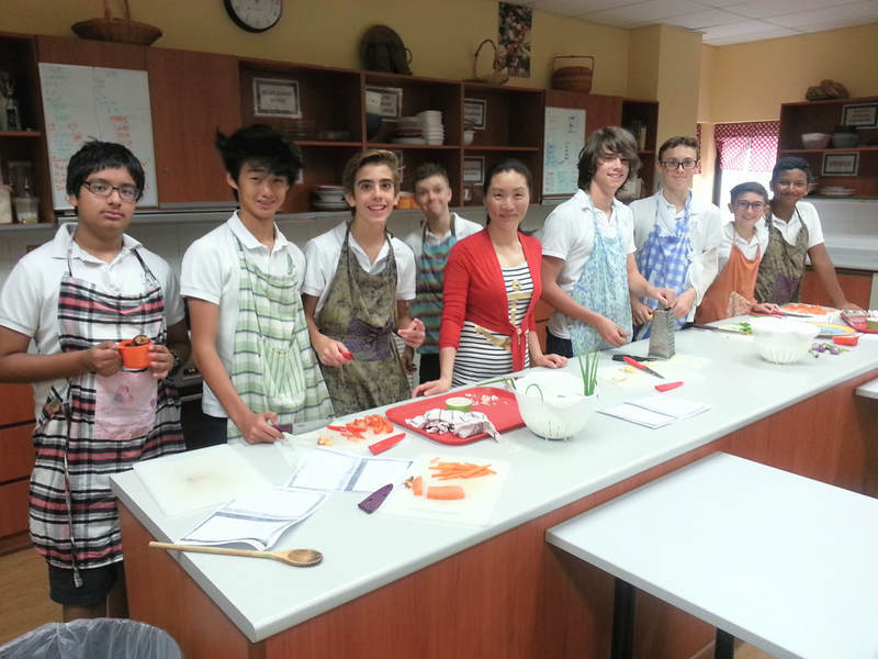 Ying and her students make dumplings during a school visit.